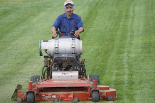 Bluegrass employee using propane powered mower